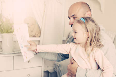 spontaneous expression: Cute blond girl giving her father a drawing, fathers day concept Stock Photo