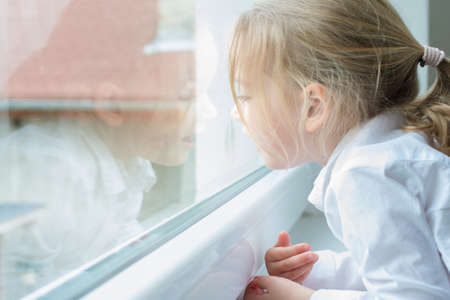 spontaneous expression: Cute blond pre school girl portrait, looking ou of the window