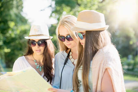 spontaneous expression: Friends looking for directions on a map at summer holidays, vacation concept Stock Photo