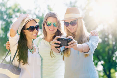 Friends taking picture at summer holidays, girls with camera taking self-portrait on their travel vacation Stock Photo