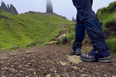 Man wearing trekking boots and gaiters walking to the Old man of Storr, Scotland Stock Photo