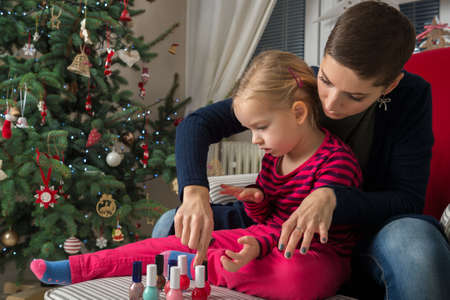 spontaneous painting: Mother and daughter having fun painting finger nails on xmas day