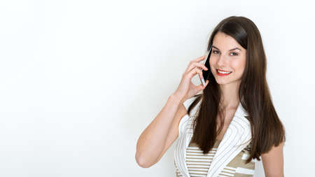 telephone call: Portrait of a positive business woman talking on phone against a white background