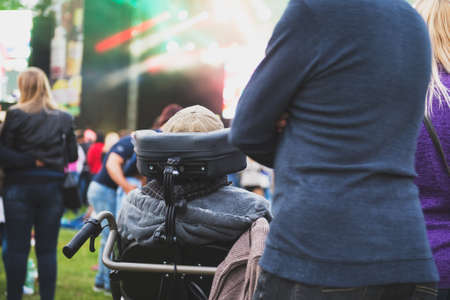 Disabled man in a special needs wheelchair watching a conecrt at a festival