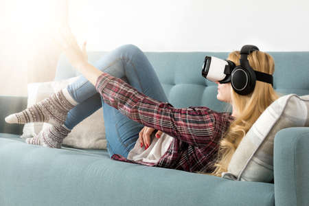 Attractive woman wearing virtual reality goggles lying on a couch. Virtual reality headset. Lifestyle virtual reality concept. Stock Photo