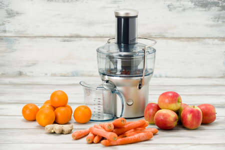 Modern electric juicer and various fruit on kitchen counter, healthy lifestyle concept Stock Photo