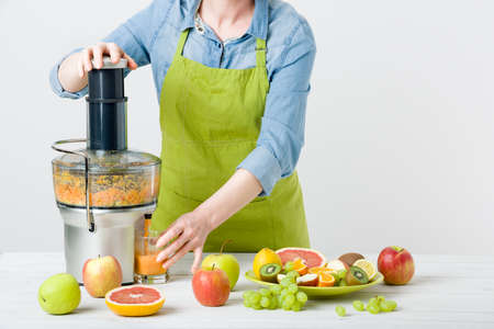 Anonymous woman wearing an apron, preparing healthy fruit juice using modern electric juicer, healthy lifestyle concept on white background
