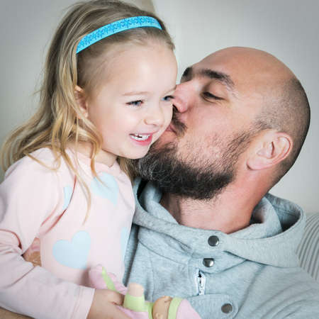 Happy father and daughter portrait, dad giving his daughter a kiss