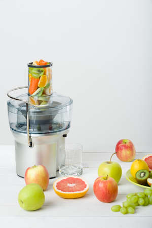 Modern electric juicer and various fruit on kitchen counter, healthy lifestyle concept. Stock Photo