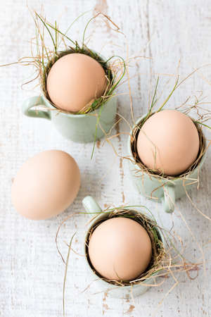 Uncolored natural easter eggs in espresso cups; happy easter concept; white wooden background Stock Photo