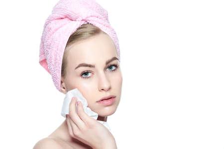 魅力的な若い金髪の女性と彼女の髪をタオルでラップをするを削除します。柔らかい表情のワイプを使用して彼女の顔をクレンジング完璧な肌を持 写真素材