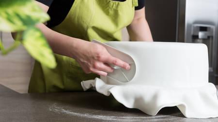 高貴なアイシングでケーキを飾るパン屋さんの女性のクローズ アップ