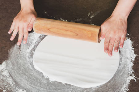 skill: Woman using rolling pin preparing royal icing for cake decorating, hands detail Stock Photo