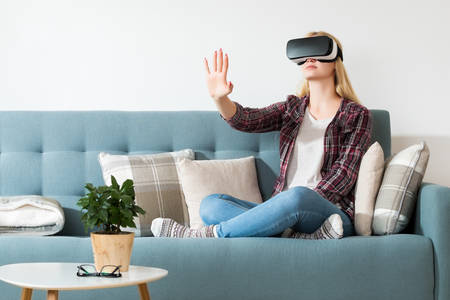 Attractive woman wearing virtual reality glasses sitting on a couch. Virtual reality headset. Lifestyle virtual reality concept. Stock Photo