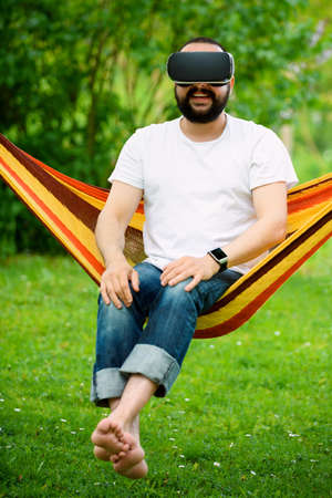 virtual reality simulator: Young bearded man wearing virtual reality goggles relaxing in a garden hammock. Lifestyle VR fun and relax concept