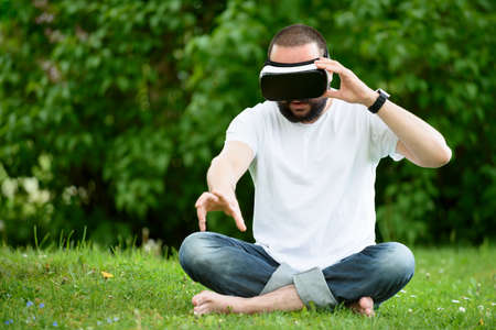 virtual reality simulator: Young bearded man wearing virtual reality goggles sitting in his garden. Lifestyle VR fun and relax concept. Stock Photo