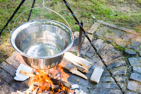 outdoor fireplace: Cooking food on fire outdoors. Cooking outdoors in cast-iron cauldron.