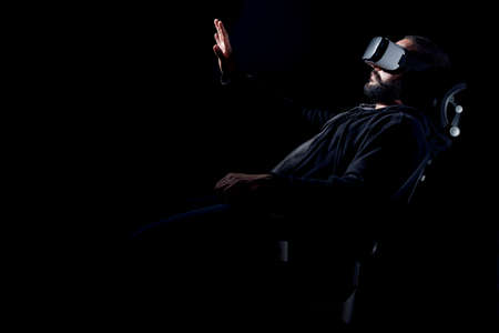 Young hipster bearded man wearing virtual reality goggles. Black background studio VR concept Stock Photo