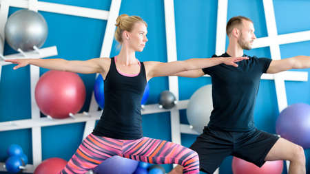 Nice couple doing yoga in a studio. Young people in yoga class in Warrior pose. Yoga group concept Stock Photo
