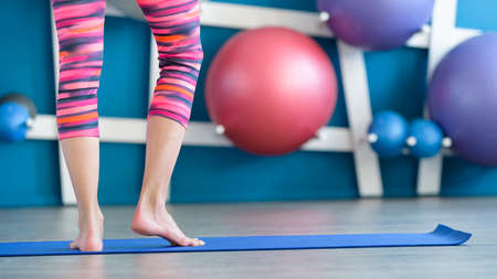 Young woman standing on blue yoga or fitness mat. Working out, healthy life, keeping fit concept