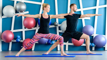 Nice couple doing yoga in a studio. Young people in yoga class in Warrior pose. Yoga group concept.