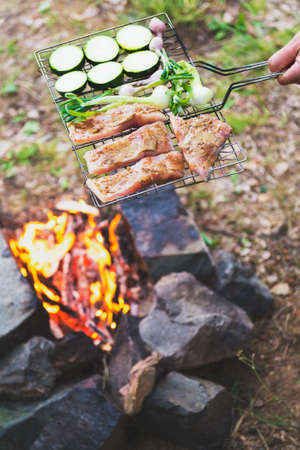 Man preparing dinner on campfire, adventure lifestyle camping vacation concept