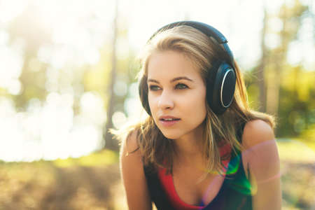 sportwoman: Young attractive sportswoman listening to music wearing headphones. Sport, fitness, workout concept
