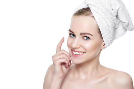 Beautiful Young Blond Woman applying Face cream under her eyes. Facial treatment. Cosmetology, beauty and spa concept. Isolated on white background. Banco de Imagens
