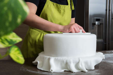 gum paste: Unrecognisable woman in bakery decorating wedding cake with white fondant