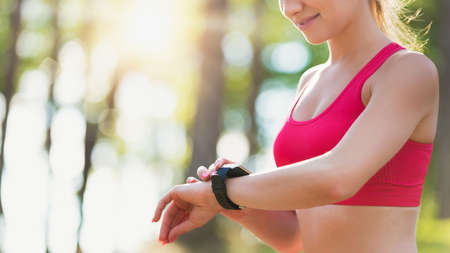 sportwoman: Attractive female athlete using fitness app on her smart watch to monitor workout performance Stock Photo