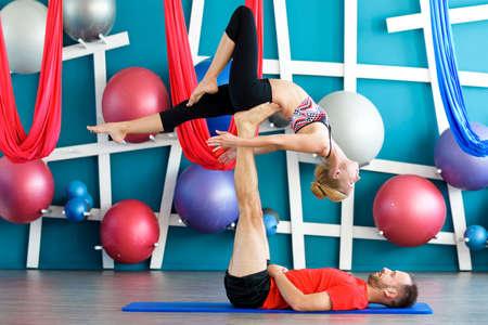 Couple practicing acro yoga in a studio. Acro yoga concept. Couple yoga class workout Stock Photo