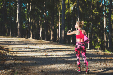 Young fit athletic woman in a forest wearing smart watch and holding yoga mat, walking away from the camera. Mind and body happiness concept Stock Photo