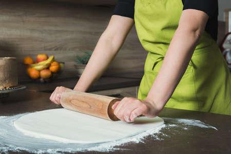 Woman using rolling pin preparing white fondant for cake decorating, hands detail