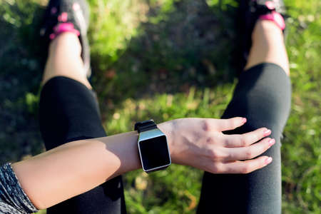 sportwoman: Close-up Shot. Sportive Woman After Workout Session Checking Fitness Results on Smart Watch. Top view shot of young woman checking fitness progress on her smart watch. Stock Photo