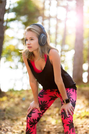 sportwoman: Young attractive sportswoman listening to music wearing headphones and checking her smart watch. Sport, fitness, workout concept