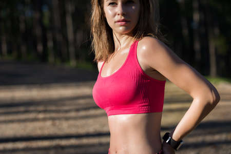 Attractive fit athletic woman standing in a forest, sweating and taking a break from intense workout. Stock Photo