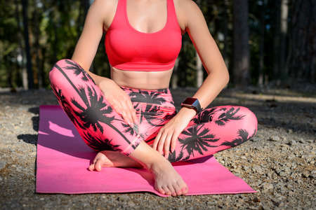 Young attractive woman with smart watch taking a break after yoga workout. Sport, fitness, workout concept