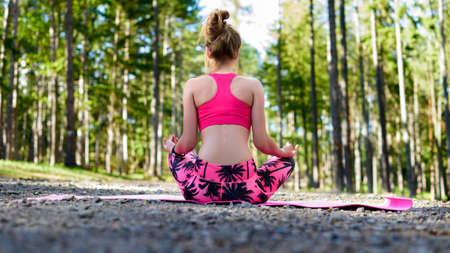 Young woman meditating in lotus position practicing yoga in a forest. Freedom concept. Relax, mind and body happiness. Stock Photo