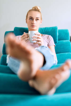 Beautiful young woman relaxing on the sofa at home, watching tv and enjoying coffee Stock Photo