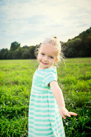 Adorable blond little girl with cheeky smile, outdoors play time Stock Photo