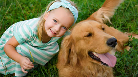 Adorable smiling little blond girl playing with her cute pet dog golden retriever