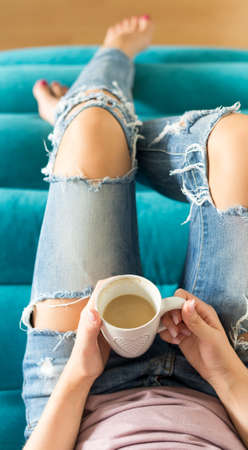 Beautiful young woman relaxing on the sofa at home, watching tv and enjoying coffee, view from above Stock Photo