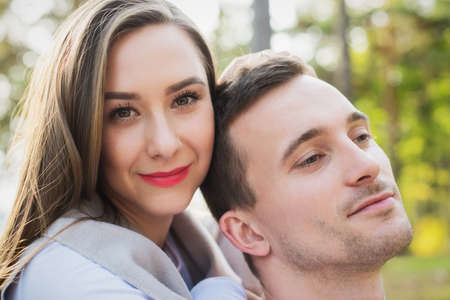 Happy young couple in love hugging. Park outdoors date. Loving couple looking at camera portrait.