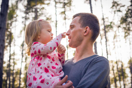 Young father holding cute toddler girl daughter in his arms and looking at her Stock Photo