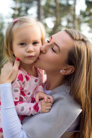 Young single mother holding cute toddler girl daughter in her arms and giving her a kiss on a cheek