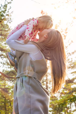 Young single mother holding cute toddler girl daughter in her arms and lifting her up in the air, both laughing