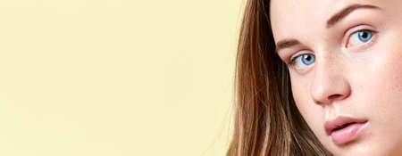 Muchacha bonita del adolescente del redhead con los ojos azules y las pecas, con los hombros desnudos, mirando la cámara. Modelo con ligero maquillaje nude, fondo amarillo. Retrato de belleza con espacio de copia. Foto de archivo - 88671951