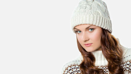 Gorgeous girl wearing warm knitted christmas jumper and a hat, xmas concept on white background with copy space