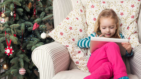 Cute preschool girl writing letter to santa on digital tablet, sitting in front of xmas tree Stock Photo