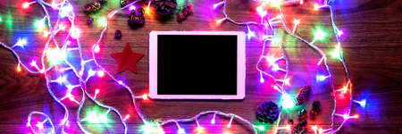 Desk view from above with digital tablet and christmas lights, xmas online shopping concept